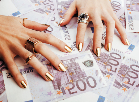 hands of rich woman with golden manicure and many jewelry rings