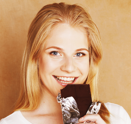 habbit: young cute blond girl eating chocolate and drinking coffee close Stock Photo