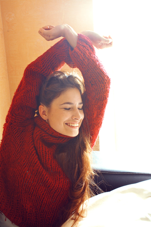 young pretty real woman in red sweater and scarf all over her fa
