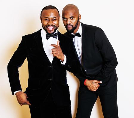 dinky: two afro-american businessmen in black suits emotional posing, gesturing, smiling. wearing bow-ties