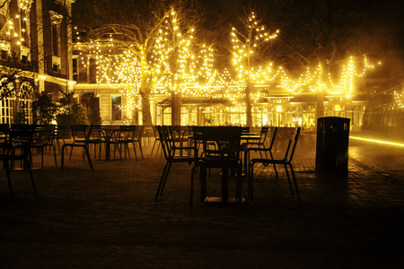 empty night restaurant, lot of tables and chairs with noone, magic fairy lights on trees like christmas celebration Stock Photo