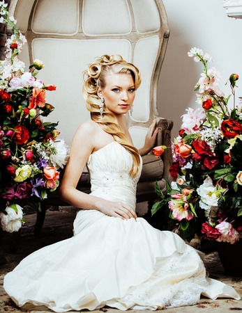 beauty young blond woman bride alone in luxury vintage interior with a lot of flowers