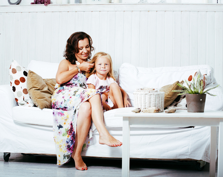 happy smiling mother with little cute daughter at home interior,