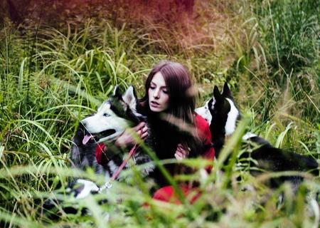 Femme en robe rouge avec des loups d'arbres, forêt, chiens husky mystère p Banque d'images - 78080320
