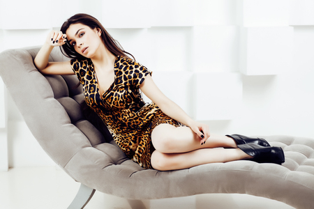 pretty stylish woman in fashion dress with leopard print together in luxury rich room interior, lifestyle people concept, modern brunette together