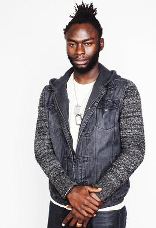 rastas: apuesto joven inconformista estilo afro estadounidense chico ensaya un emocional aislado en fondo blanco sonriendo, la gente concepto de estilo de vida