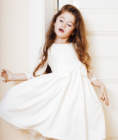 little cute girl at home, opening door well-dressed in white dre