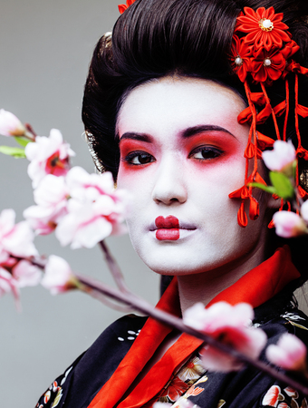ethno: young pretty geisha in black kimono among sakura, asian ethno close up