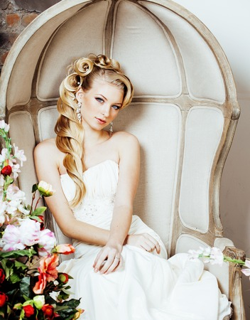 luxe: beauty young blond woman bride alone in luxury vintage interior with a lot of flowers
