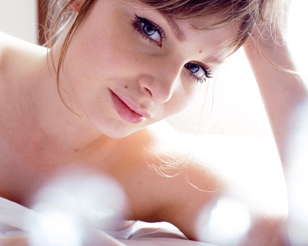 one sheet: pretty blond real woman laying in bed Stock Photo