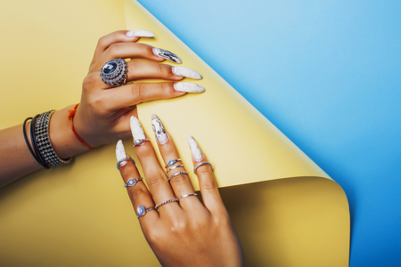 woman hands holding colorful paper copyspace wearing a lot of oriental jewelry rings, mulatto indian girl concept