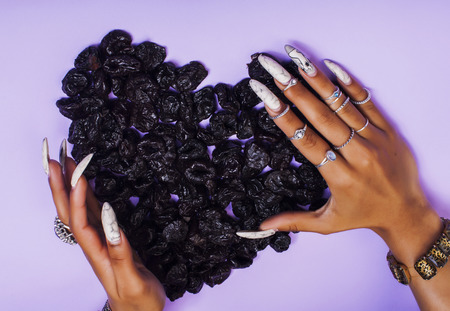 woman hands with long nails manicure holding fruits in shape of heart on purple background