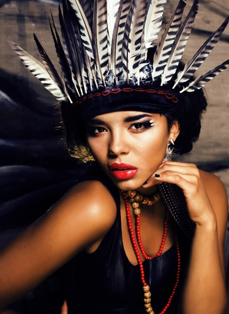 young pretty woman with make up like North American indian, feather in hair, fashion halloween concept creative