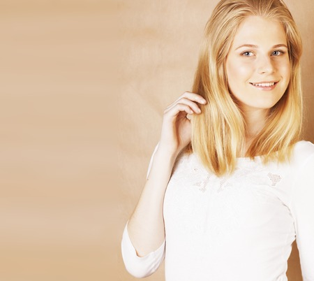young cool blong teenage girl messed with her hair smiling close up on warm brown background, lifestyle people concept