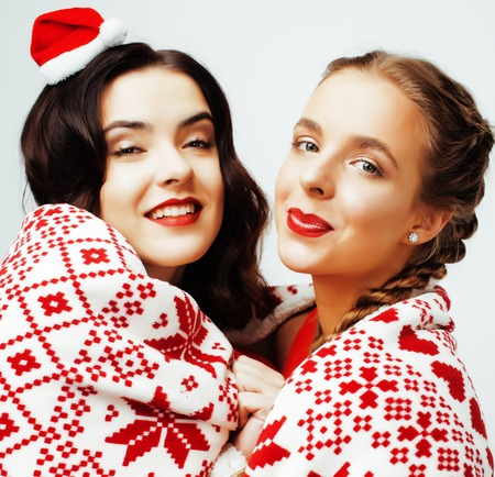 winter fashion: young pretty happy smiling blond and brunette woman girlfriends on christmas in santas red hat and holiday decorated plaid, lifestyle people concept close up Stock Photo