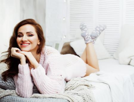 彼女の寝室での若いかわいいブルネットの女性は、窓に座って、幸せな笑顔のライフスタイル人々の概念がクローズアップ 写真素材