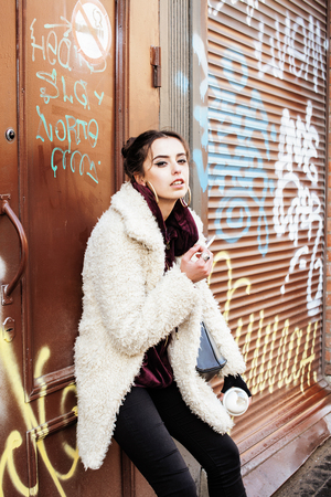 young pretty stylish teenage girl outside in city wall with graf