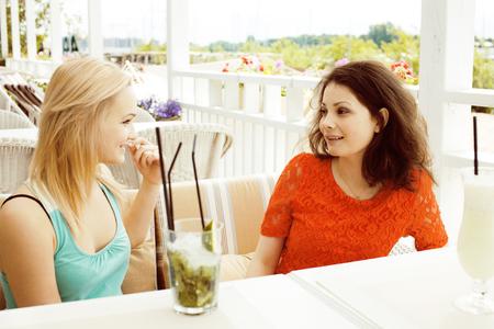 portrait of two pretty modern girl friends in cafe open air inte