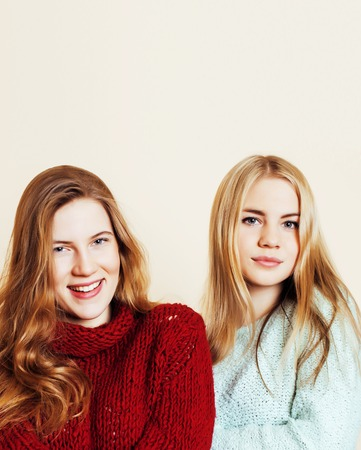 Two young girlfriends in winter sweaters indoors having fun.