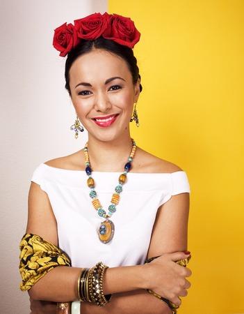 黄色の背景に幸せを笑う若いかわいいメキシコの女性、l