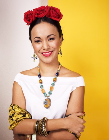 young pretty mexican woman smiling happy on yellow background, l