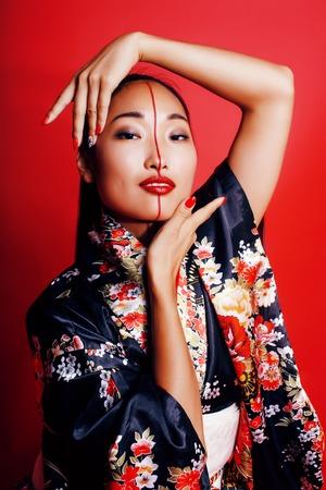 young pretty geisha on red background posing in kimono, oriental 版權商用圖片