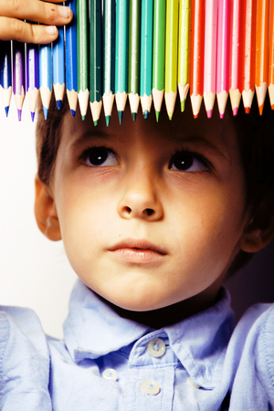 little cute boy with color pencils close up smiling, education f
