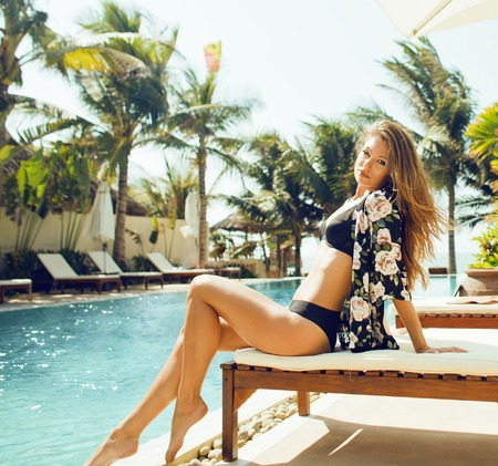 young pretty woman at swimming pool relaxing in chair, fashion look in lingerie at hotel close up smiling Stock Photo