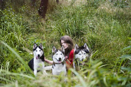 woman in red dress with tree wolfs, forest, husky dogs mystery p Banque d'images - 99958053