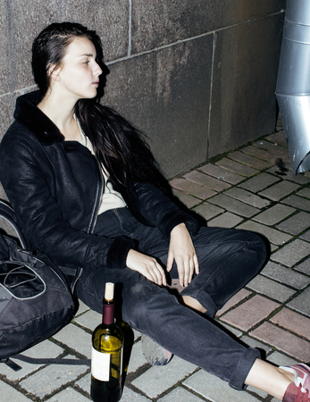 young poor ttenage girl sitting at dirty wall on floor with bott Stock Photo