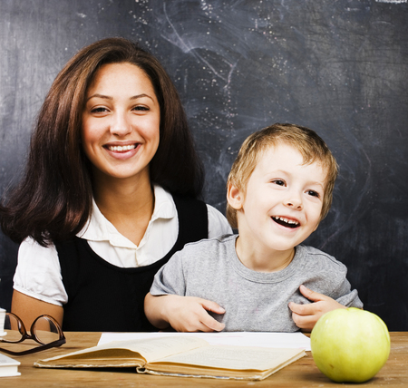 little cute boy with teacher in classroom smiling, lifestyle peo Imagens