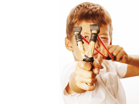 little cute angry real boy with slingshot isolated Foto de archivo