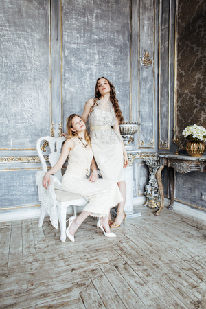 two pretty twin sister blond curly hairstyle girl in luxury house Archivio Fotografico