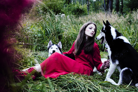 woman in red dress with tree wolfs, forest, husky dogs mystery p Banque d'images - 103522891