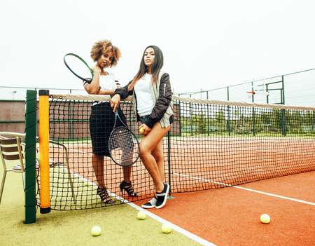 young pretty girlfriends hanging on tennis court, fashion stylis Stock Photo