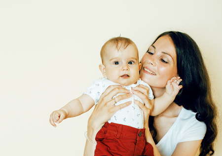 young brunette happy mother holding toddler baby son, breast-fee