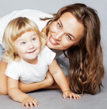 young modern smiling blond mother with little cute daughter