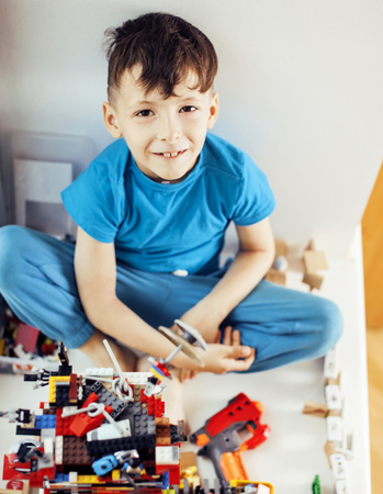 little cute preschooler boy playing toys at home happy smiling,