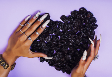 woman hands with long nails manicure holding fruits in shape of
