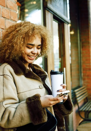 young pretty african american women drinking coffee outside, lif
