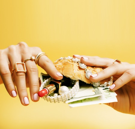 woman hands holding hamburger with money, jewelry, cosmetic.