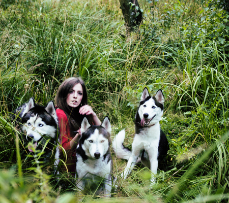 woman in red dress with tree wolfs, forest, husky dogs