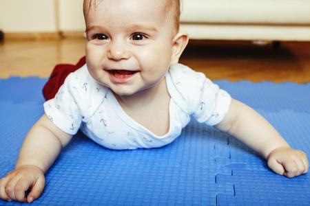 kleines süßes Baby Kleinkind auf Teppich Nahaufnahme lächelnd Standard-Bild