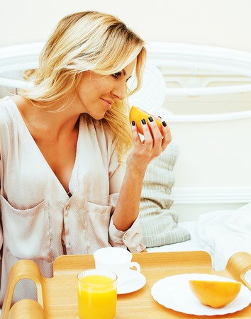 young beauty blond woman having breakfast in bed early sunny morning