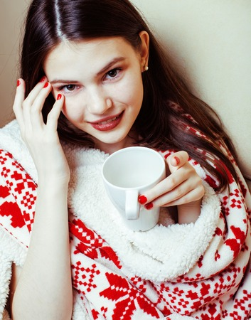 young pretty real woman in sweater and winter Christmas blanket