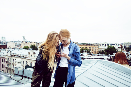 two cool blond real girls friends making selfie on roof top Stockfoto
