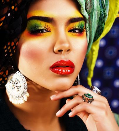 Belleza mujer brillante con maquillaje creativo, muchos chales en la cabeza. Foto de archivo