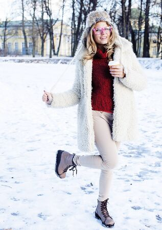 young pretty teenage hipster girl outdoor in winter snow park