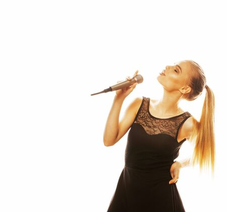 young pretty blond woman singing in microphone isolated close up Stock Photo