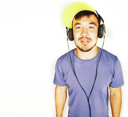 young asian man in hat and headphones listening music on white background Imagens